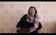 A folk singer wears traditional Tibetan clothing while singing.